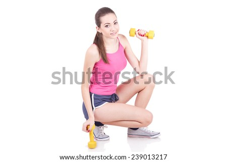 Young woman smiling while using dumbbells against a white background - stock photo