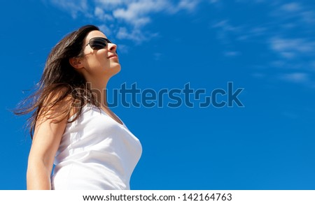 Young Woman Smiling with a Bright Blue Sky Background - stock photo