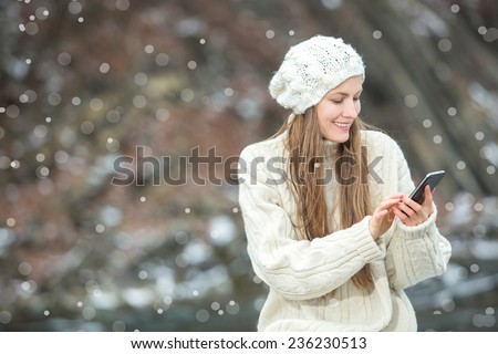 Young  woman smiling with smart phone and winter landscape and snowflakes on the background - stock photo