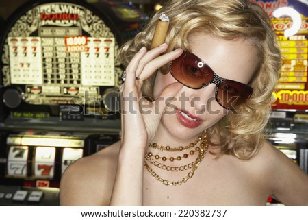 Young woman smoking a cigar in a casino - stock photo