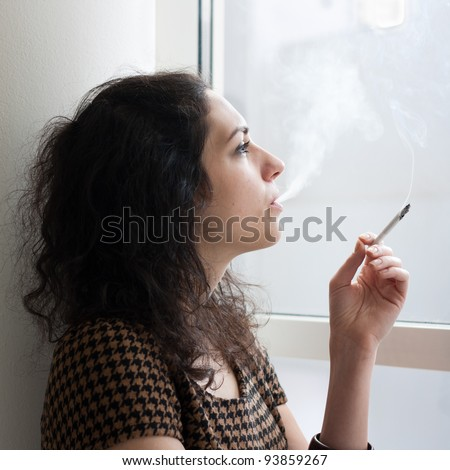 Young woman smoking indoors at a window - stock photo