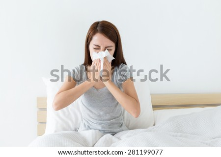 Young woman sneeze on bed - stock photo