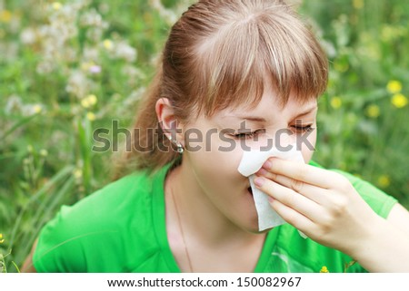 Young woman sneezing in a flowers meadow. Concept: seasonal allergy  - stock photo
