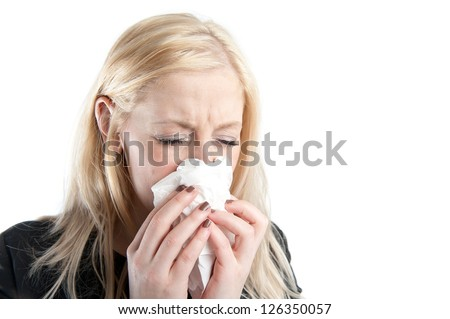 Young woman sneezing into a tissue - stock photo