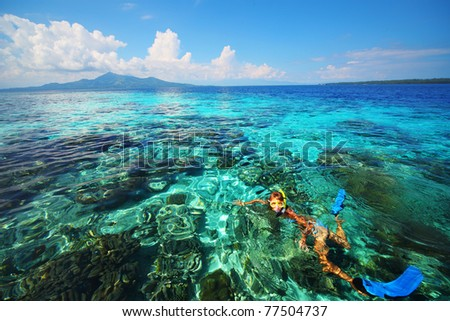 Young woman snorkeling in coral reef in tropical sea. Bunaken island. Indonesia - stock photo