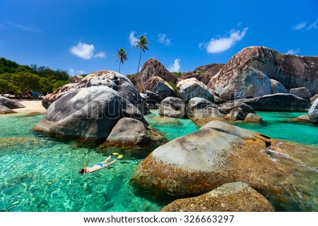 Young woman snorkeling in turquoise tropical water among huge granite boulders at The Baths beach area major tourist attraction on Virgin Gorda, British Virgin Islands, Caribbean - stock photo