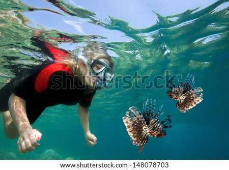Young woman snorkeling with lionfish - stock photo