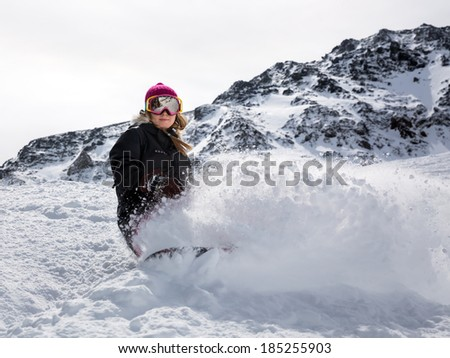 Young woman snowboarder in motion on snowboard in mountains - stock photo
