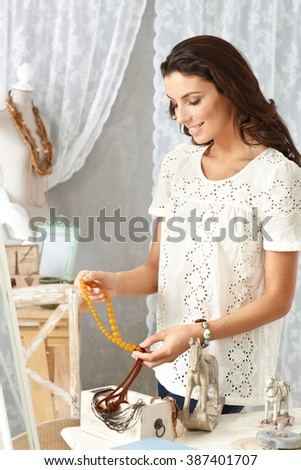 Young woman sorting accessories from wooden box at old-fashioned home, smiling. - stock photo