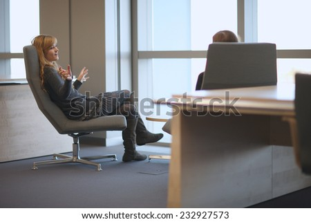 Young woman speaking emphatically with a colleague in the office - stock photo