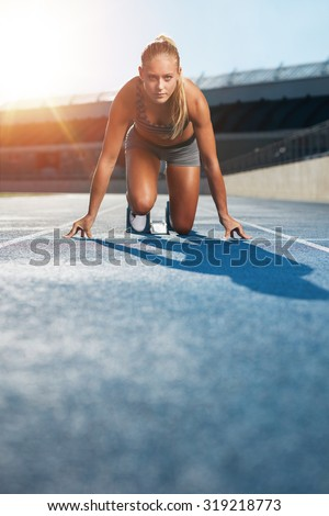 Young woman sprinter in the starter position on a race track at a sports stadium looking up at camera with determination. Runner on racetrack starting blocks. - stock photo