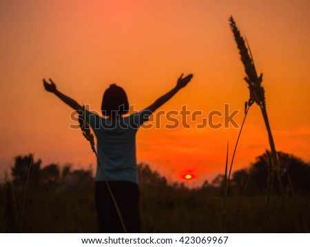 Young woman standing alone in a field during sunset. Silhouette of a young girl outdoor. blur style. - stock photo