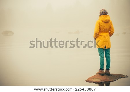 Young Woman standing alone outdoor Travel Lifestyle and melancholy emotions concept  winter foggy nature on background  - stock photo