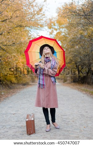 Young woman standing alone with vintage suitcase and umbrella hitchhiking on empty autumn road outdoors. Travel abroad - stock photo