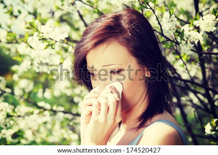 Young woman standing among blossom trees during sunny day  and wiping her nose. Girl with runny nose, having allergy and holding a tissue next to her face. - stock photo