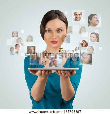 Young woman standing and smiling with many different people's faces flying from her tablet computer. Technology social media network concept - stock photo