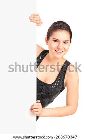 Young woman standing behind a blank panel isolated on white background - stock photo