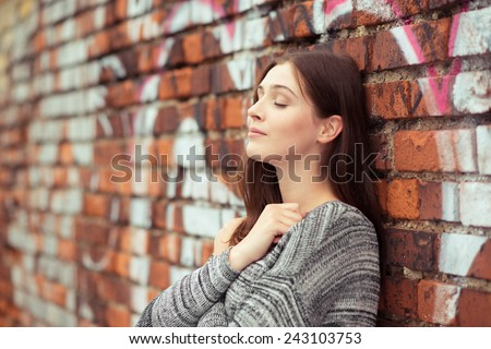 Young woman standing daydreaming or meditating as she unwinds while leaning on a brick wall with her eyes closed and a look of serenity - stock photo
