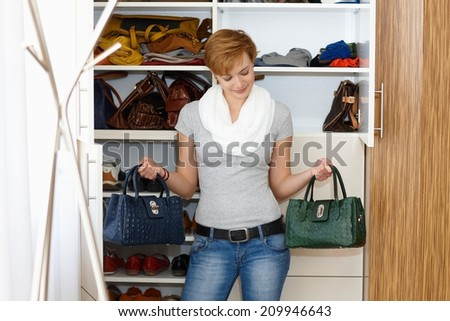 Young woman standing front of wardrobe, unable to decide which bag to take. - stock photo