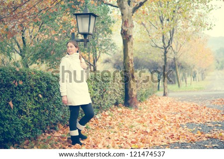 Young woman standing in a beautiful autumn scenery - stock photo