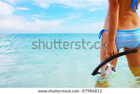 Young woman standing in a sea and holding a mask and snorkel - stock photo