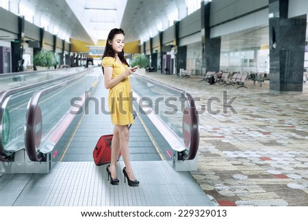 Young woman standing in airport corridor while carrying luggage and texting with mobilephone - stock photo
