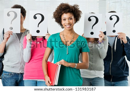 Young Woman Standing In Front Of Friends Holding Paper With Question Marks - stock photo
