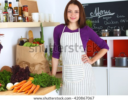 Young woman standing in her kitchen near desk with shopping bags - stock photo