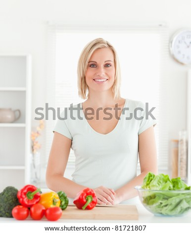 Young woman standing in kitchen smiling into camera - stock photo