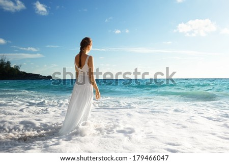young woman standing in sea waves  - stock photo