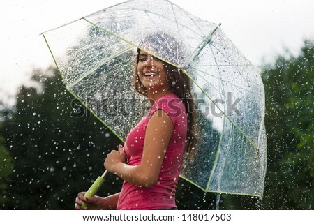 Young woman standing in summer rain with umbrella  - stock photo