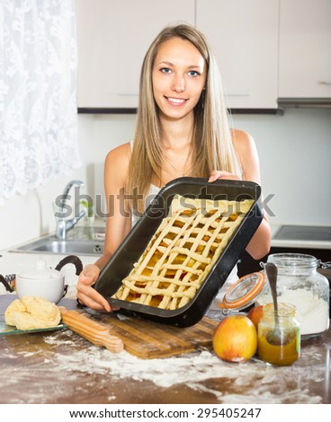 Young woman standing in the kitchen with a pie in hand and smiling - stock photo