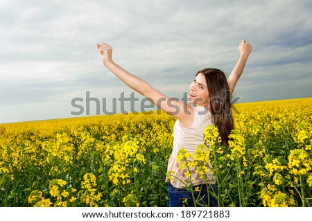 Young woman standing in yellow rapeseed field raising her arms expressing happiness and freedom. Blue sky background! - stock photo
