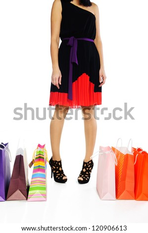 Young woman standing near colorful shopping bags isolated on white - stock photo