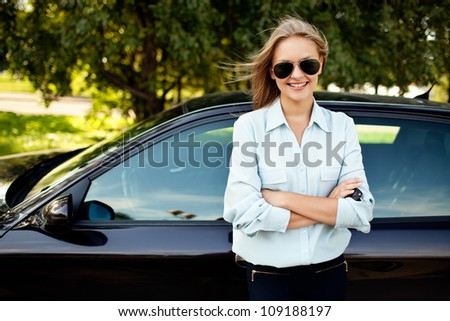 Young woman standing next to her new car - stock photo