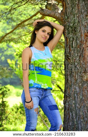 Young woman standing next to tree and smiling - stock photo