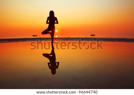 Young woman standing on a beach and relaxing - stock photo