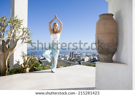 Young woman standing on balcony in tree pose yoga stance, portrait - stock photo