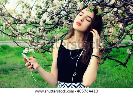 Young woman standing on the meadow at the blooming tree , using smartphone to listening music with headphone - stock photo