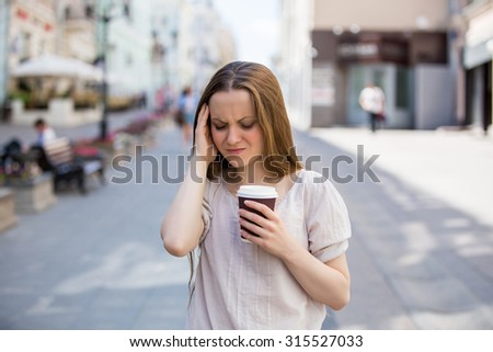 Young woman standing on the street suffering from pain. She has a take away cup of coffee and touch her temple - stock photo