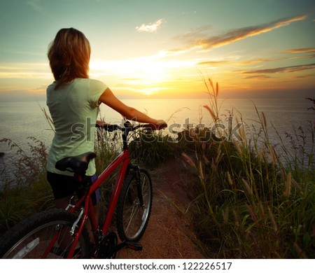 Young woman standing on top of a hill with mountain bike and enjoying the sunset sea view - stock photo