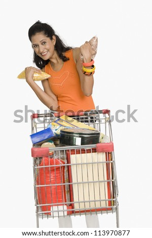 Young woman standing with a shopping cart and smiling - stock photo