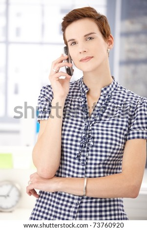 Young woman standing with cellphone, listening to phone call, smiling.? - stock photo