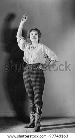 Young woman standing with her hand raised and smiling - stock photo