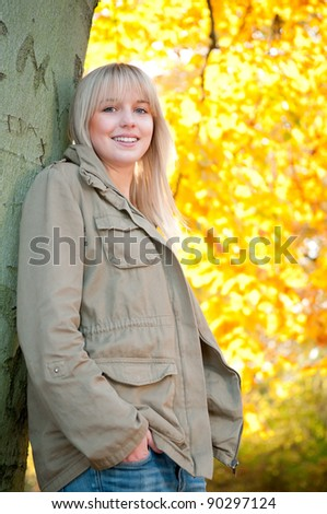 young woman stands on a tree - stock photo