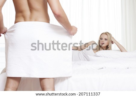 Young woman staring at nude man holding towel in bedroom - stock photo