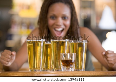 Young woman staring excitedly at a round of beers - stock photo