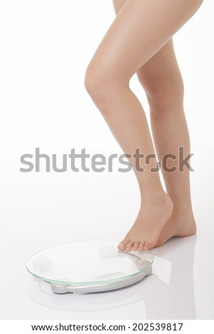 Young woman stepping onto scales isolated on a white background - stock photo