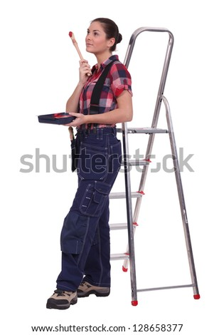 Young woman stood by ladder with paint brush - stock photo