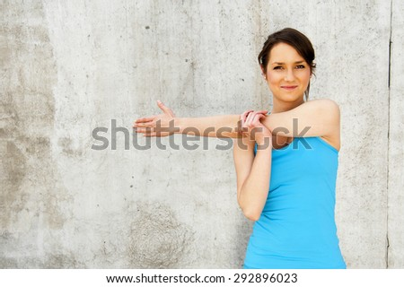 young woman stretching after run by the wall in city with big smile. in blue sportswear. - stock photo